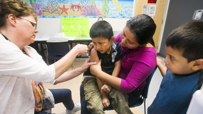 Maricopa County Public Health Immunization nurse Diane Dickinson administers a measles vaccine to Jose Nix, 6, of Phoenix, who sits on the lap of her mother, Rosaura Nix of Phoenix, as Jose's brother, Ada Nix, 4, who also got the measles vaccine looks on, at the Maricopa County Public Health Immunization Clinic in Phoenix on Thursday, January 22, 2015.