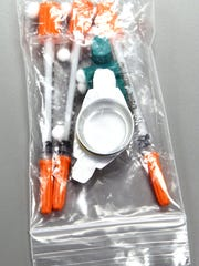 "A sample ""cooker kit"" used by drug addicts. It contains syringes, small caps for liquifying the drug and small cotton swabs."