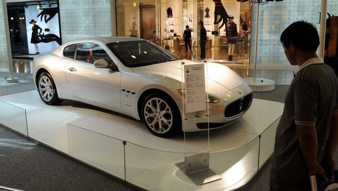 A man looks at a Maserati in Shanghai. The population of Asian millionaires is rising.