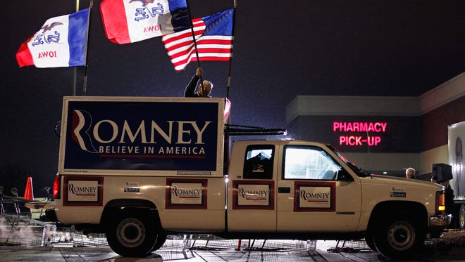 Jim Wilson of Buckingham, Va., posts United States and Iowa flags on the back of his pickup truck before the start of a campaign rally with Mitt Romney on Dec. 30, 2011, in West Des Moines, Iowa.