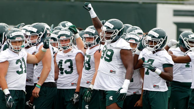 Michigan State defensive players, including Edward Warinner (31), Jack Mandryk (43), Raequan Williams (99) and Michael Dowell (7), gather at MSU's first practice, Thursday, Aug. 2, 2018, in East Lansing, Mich.