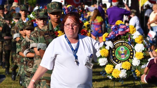 Before the opening ceremonies of the 31st Annual Vietnam and All Veterans Reunion at Wickham Park Monday night, more that 75 wreaths were presented and placed before The Wall. Donna Rogers, secretary of the Vietnam and All Veterans Reunion, had the honor of placing the first wreath.