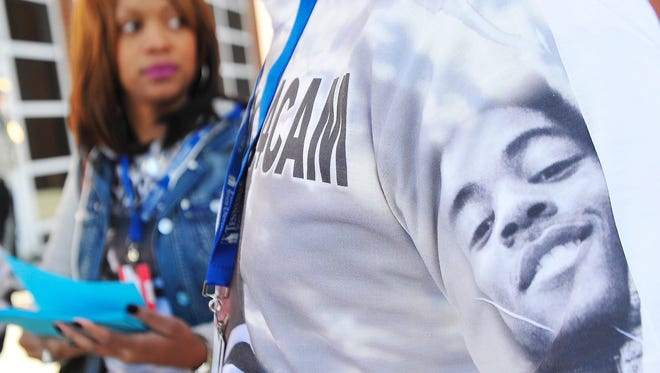 Stacie Payne, mother of Cameron Selmon (pictured on sweatshirt), hands out fliers to students on the campus of Tennessee State University in hopes of finding those responsible for her son's death in October.