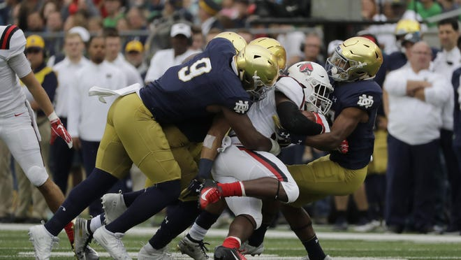 FILE - In this Sept. 8, 2018, file photo, Notre Dame's Daelin Hayes (9) and cornerback Julian Love, right, tackle Ball State running back Caleb Huntley, center, during the first half of an NCAA college football game in South Bend, Ind. No. 4 Notre Dame heads into Saturday night's, Nov. 7, 2020, showdown against No. 1 Clemson allowing just 10.3 points per game.