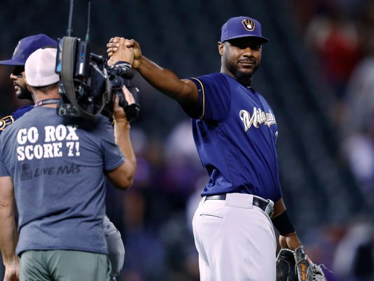 Milwaukee Brewers first baseman Chris Carter, center, is congratulated by teammates after helping to retire the Colorado Rockies in the 10th inning of a baseball game Saturday, Oct. 1, 2016, in Denver. Milwaukee won 4-3 in 10 innings. Carter hit a solo home run to provide the margin of victory. (AP Photo/David Zalubowski)