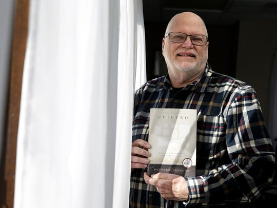 """John Wiley holds a copy of """"Evicted"""" by Matthew Desmond."""