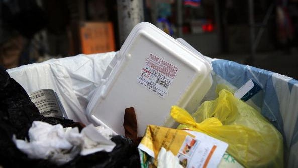 A polystyrene foam take-out container is viewed in a trash can in New York City. New York's City Council voted to ban single-use items like these containers.