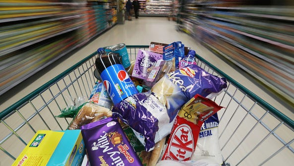 A shopping trolley full of grocery products is pushed along an aisle in this arranged photograph at a Morrisons supermarket, operated by William Morrisons Supermarkets Plc, in Crawley, U.K., on Tuesday, March 3 2015. Wm Morrison Supermarkets Plc named David Potts as chief executive officer, tasking the former head of Tesco Plc's Asia unit with reviving the ailing British grocer. Photographer: Chris Ratcliffe/Bloomberg via Getty Images