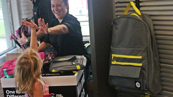 Cori Odom from TCC high-fives Audri Crews after giving her a coveted pink backpack at a previous free backpack giveaway in Florida.