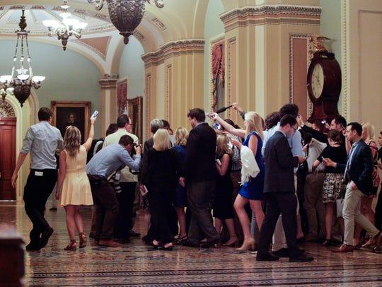 Members of media surround a Republican lawmaker through