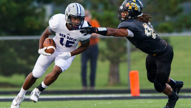 Ben Davis High School senior Trew Smith (15) breaks past the tackle of Avon High School junior Zach Betustak (45) during the first half of action. Avon High School hosted Ben Davis High School in varsity football Friday, August 29, 2014.