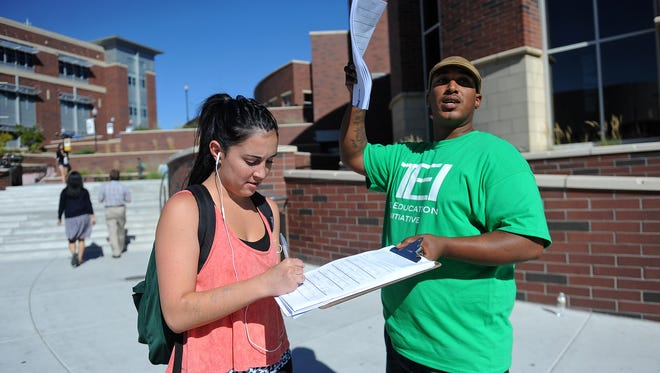 Petitioner Craig Morgan, right, collects a signature in 2012 from UNR student Katherine Garcia for a petition to support the Education Initiative to create a margin tax on some Nevada businesses.