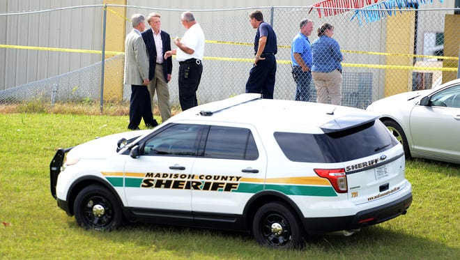 Sheriff John Mehr talks with investigators at the scene of a shooting in Three Way on Friday.