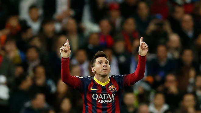 Barcelona's Lionel Messi from Argentina, left, celebrates his goal  during a Spanish La Liga soccer match between Real Madrid and FC Barcelona at the Santiago Bernabeu  stadium in Madrid, Spain, Sunday.