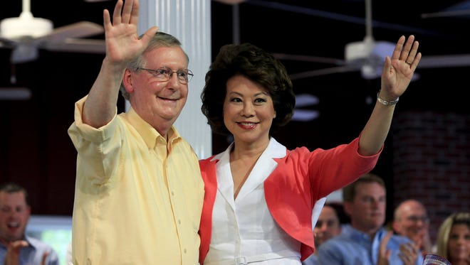 Sen. Mitch McConnell, left, and his wife Elaine Chao wave to the crowd after his speech at the Fancy Farm Picnic, Aug. 2, 2014