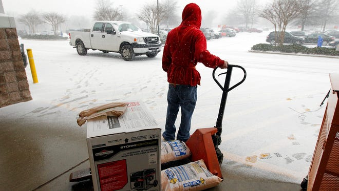 In this photo store worker Chris Craft pulls a generator and some sand out to the front for a customer at the Home Depot in Cary, N.C.