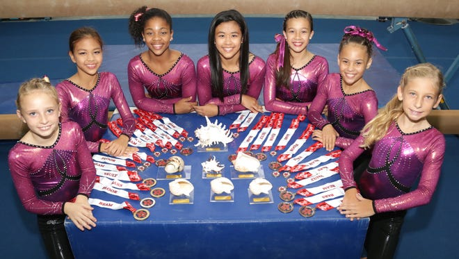 Members of the Island Twisters Gymnastics show off their 2016 Aloha Gymfest medals and seashell trophies. From left: Lillian McClellan, Elizabeth Mamczarz, Qaydenz Montgomery, Eileen Mamczarz, Janine Miller, Isabella Kebreau, Phaedra Redman.