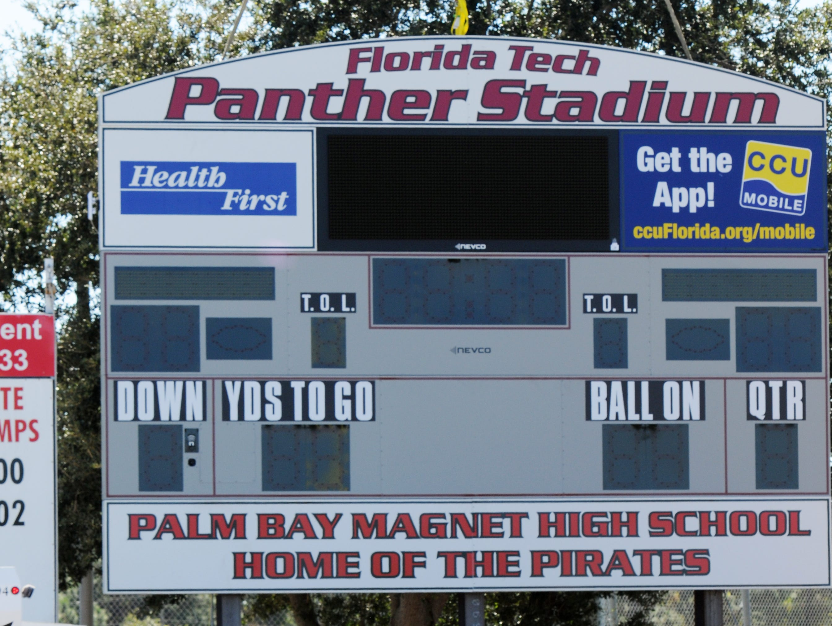 Officials from Florida Tech and Palm Bay High School watch as workers install the new scoreboard sign at Panther Stadium in Melbourne Friday.