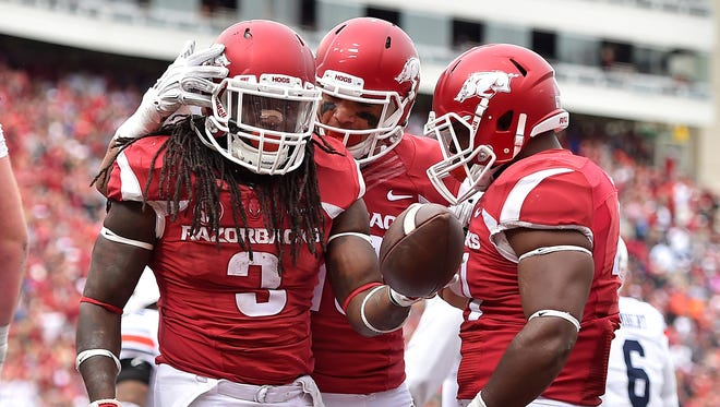 Arkansas Razorbacks running back Alex Collins (3) celebrates with teammates after scoring a touchdown against the Auburn Tigers during the second half at Donald W. Reynolds Razorback Stadium.
