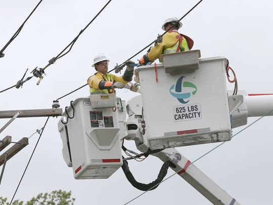Duke Energy workers repair a power line. File photo by Matt Kryger / The Star