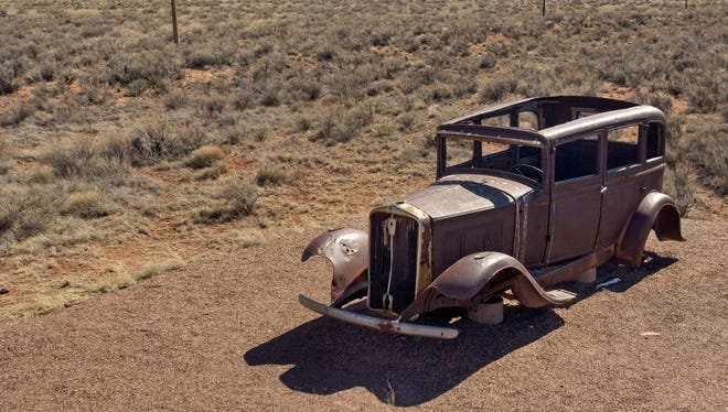 An old car sits at the site of where the historic Route 66 (crossed through Petrified Forest National Park.