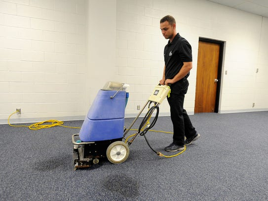Alex Acuna uses a carpet extractor to clean up some