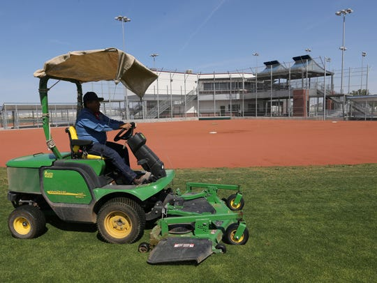 Jose Luis Martinez mows the lawn on one of the fields