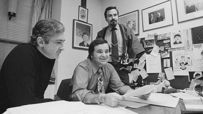 'Mad' magazine Editor Al Feldstein, center, sits with Art Director John Putnam, left, and a freelancer named Jack, at the magazine's New York headquarters in 1972. Feldstein, whose 28 years at the helm of 'Mad' transformed the satirical magazine into a pop-culture institution, died April 29, 2014. He was 88.