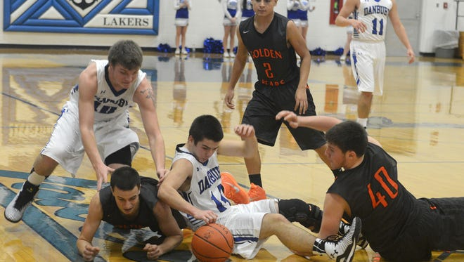 Players get tangled up as the fight for the loose ball during a basketball game on Monday, Dec 15, 2014.