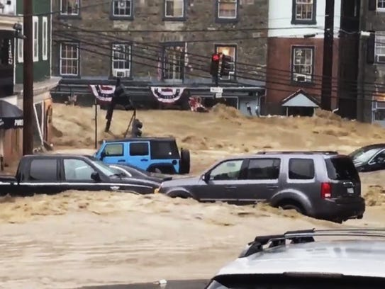 Water rushes through Main Street in Ellicott City,