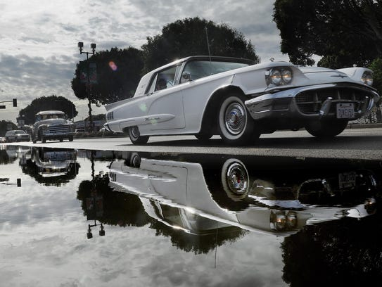 A classic Thunderbird is reflected in a puddle of water