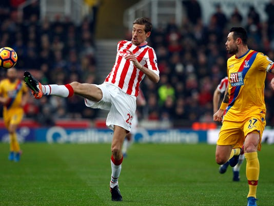 Stoke City's Peter Crouch controls the ball  past  Crystal Palace's Damien Delaney, during the English  Premier League soccer match between Stoke City and Crystal Palace, at the bet365 Stadium, in Stoke, England, Saturday, Feb. 11, 2017. (Martin Rickett/PA via AP)