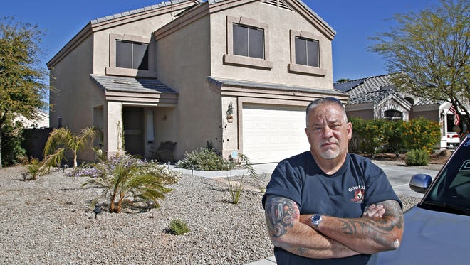 Ken Butters outside of his El Mirage home. His HOA has issued a demand upon he and nearly 700 of his neighbors to repaint their homes. Butters is taking the stand that the paint on his home is in good condition and does not need repainting which could cost him $2,000.