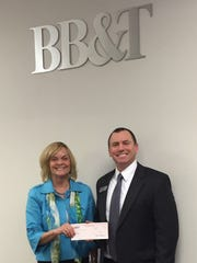 Barbie Kauffman Matthie, president of the board for House of Hope, receives EITC funding from Crawford McFerran, senior VP of business services at BB&T Bank.