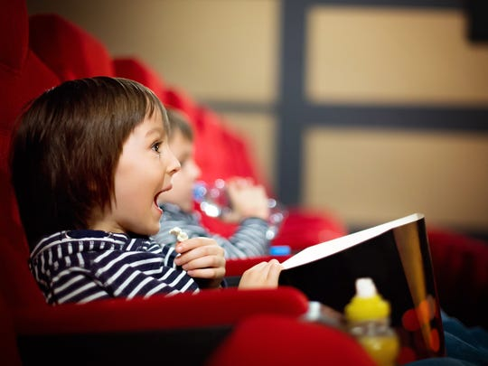 Two preschool children watching movie, eating popcorn