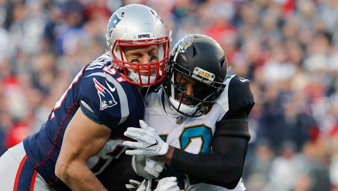 Patriots tight end Rob Gronkowski is hit by Jaguars strong safety Barry Church.