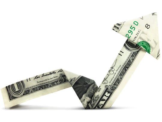 Dollar bill folded like an arrow and pointed up.