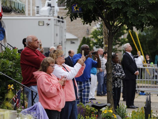 Neighbors across the street from St. Anthony of Padua Church take photos with their phones and cameras as the hearse arrives for Beau Biden viewing in Wilmington Friday.