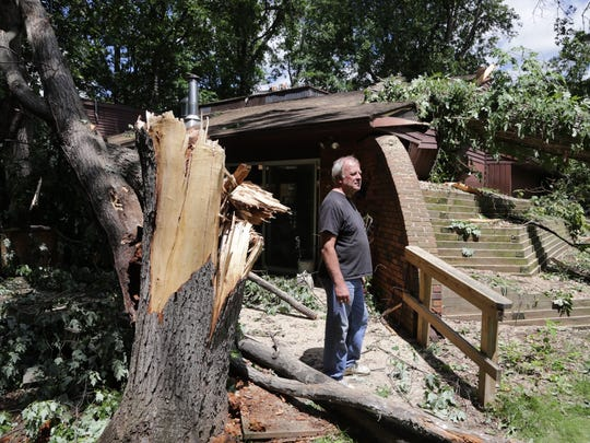 Russ Reed of Hubbard Lake looks over damage to the