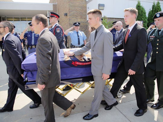 Pallbearers carry the casket out, after the funeral