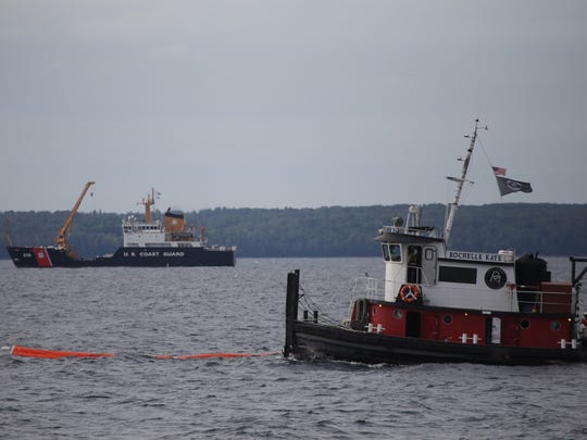 The tug Rochelle Kaye, foreground, and the U.S. Coast Guard cutter Alder take part in a demonstration of boom deployment and shoreline cleanup assessment techniques during the Enbridge emergency response exercise at the Straits of Mackinac on Thursday, Sept. 24, 2015.