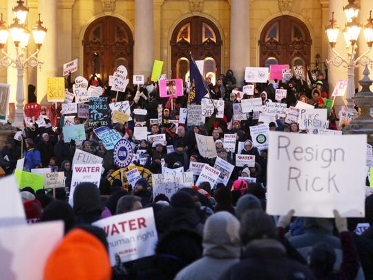 Hundreds of protesters fill the front steps of the State Capitol Building in Lansing on Tuesday, Jan. 19, 2016, while shouting for the removal of Governor Rick Snyder before his State of the State address for his role in the Flint water crisis.