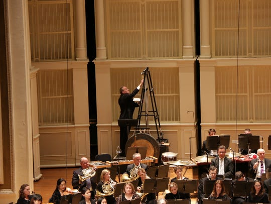 CSO percussionist Richard Jensen climbs a ladder to