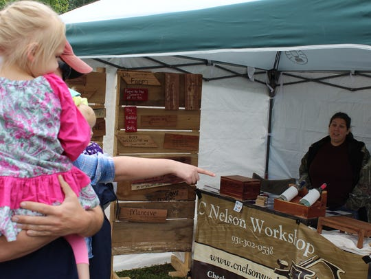 Customers check out the woodworking goods of C Nelson