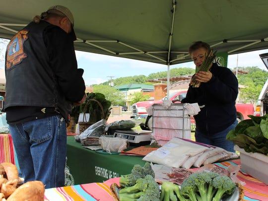 Pat Pangle sells fresh greens to a customer.