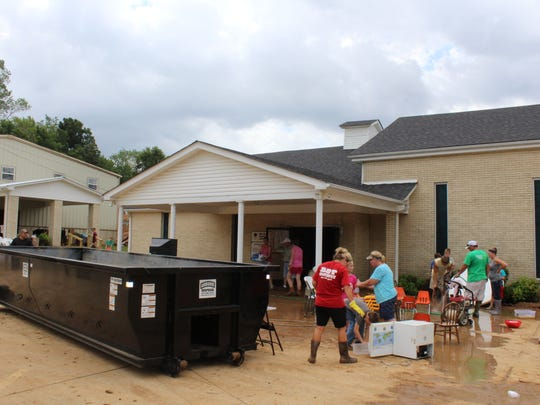 Volunteers and church members work to salvage anything