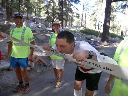 Cory Reese kisses the tape at the finish line of the