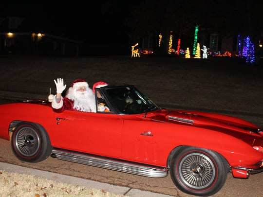 Santa waves from his red convertible during Lakeland's