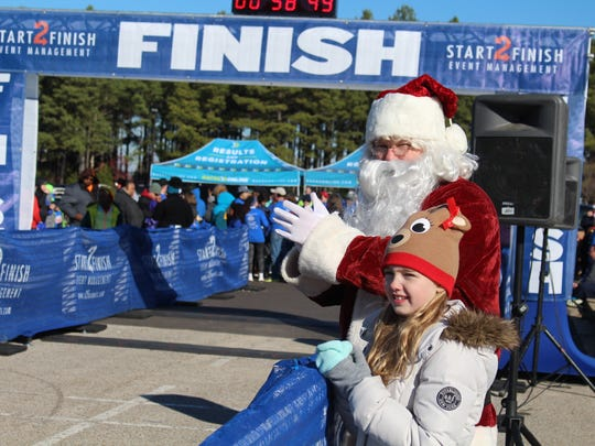Santa and Katie Welch, 8, cheered on runners from the sidelines of the Run Run Rudolph 5K at Rivercrest Elementary School, Saturday, Dec. 10.