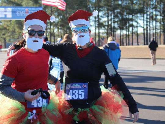 Running Santas, Emily Nelson (left), 27, of Memphis, and Emily Weeks, 34, of Southaven, finished the race within less than a second of each other. Nelson's time was 26:49:84. Weeks finished at 26:50:07.